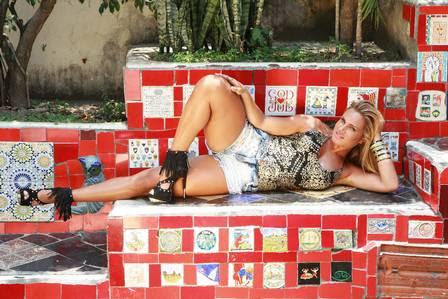 A loura usa short com spikes Fill Sete, blusa bordada FG, sandália de franja Luz da Lua e pulseiras Karina