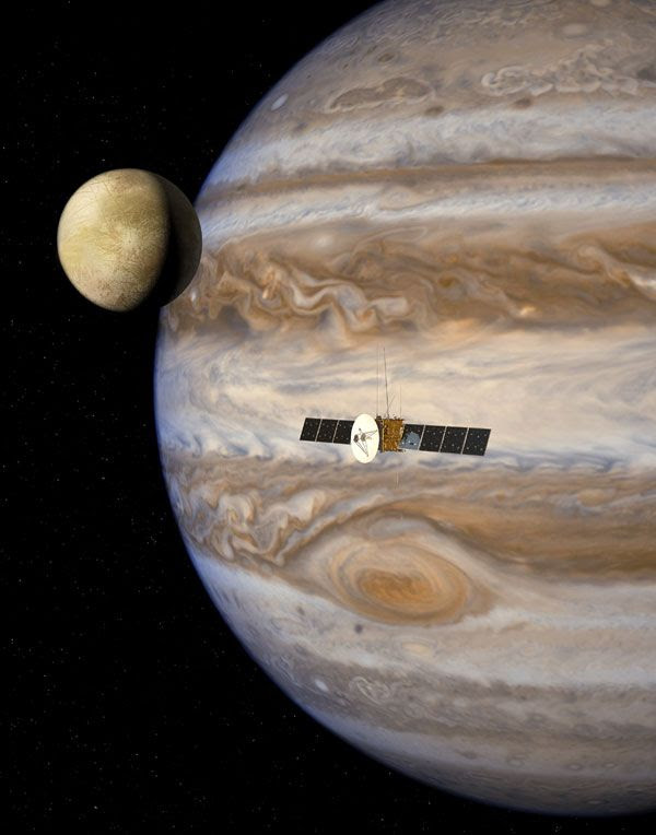 An artist's concept of ESA's JUICE spacecraft flying by Jupiter and one of its Galilean moons.