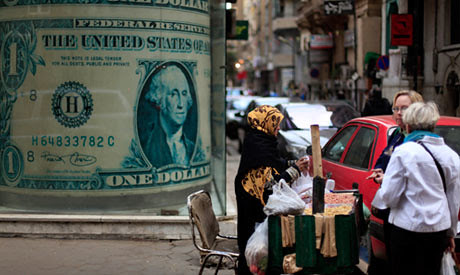 Vendor on the streets of Cairo, Egypt with an enlarged US dollar advertisement in the background. Egypt is facing a renewed economic crisis due to its alliance with imperialism. by Pan-African News Wire File Photos