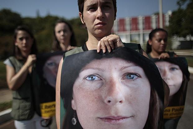 Ativistas do Greenpeace seguram faixa com imagem da brasileira Ana Paula Maciel durante protesto em frente à Embaixada da Rússia em Brasília, nesta sexta (27) (Foto: Ueslei Marcelino/Reuters)