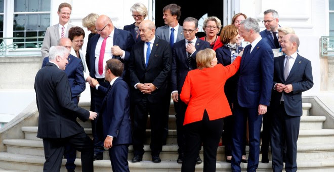 La canciller alemana Angela Merkel y el presidente francés Emmanuel Macron, con sus ministros, antes para posar para la foto de familia de la cumbre franco-germana, en el Palacio de Meseberg. REUTERS/Hannibal Hanschke