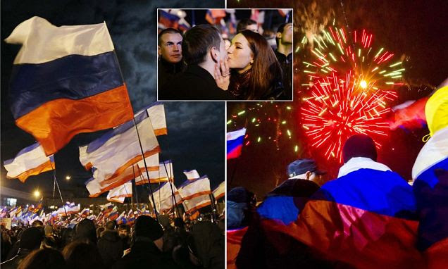 Jubilant crowds let off fireworks (right), waved Russian flags (left) and celebrated in Lenin Square in the Crimean capital of Simferopol tonight after 95 per cent of voters backed leaving Ukraine and passing control of the region to Moscow