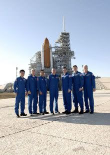 The crew of STS-119 pose in front of space shuttle Discovery at Launch Pad 39-A at Kennedy Space Center, Florida, on January 20, 2009.