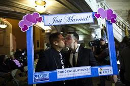 Brian Hirschberg (R) kisses his partner Gabriel Laureano holding up a frame while they attend marriage ceremonies of gay, lesbian and straight couples in Newark, New Jersey October 21, 2013. REUTERS-Eduardo Munoz