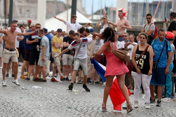 A French woman (in pink) throws a beer bottle towards English football fans as they gather in the old town area of Marseille ahead of the first game in Euro 2016
