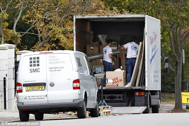 Removal men appear to pack furniture and other items on to the back of the van on Friday