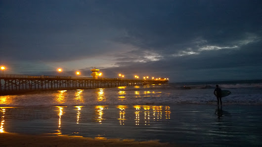 Seal Beach Pier and a surfer walking out at the edge of Dark