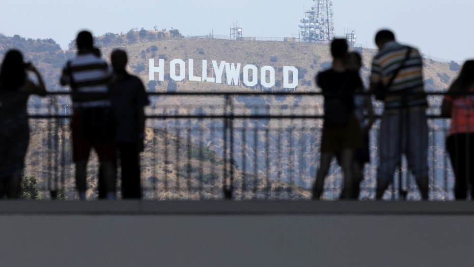 FILE -- Tourists take pictures of the Hollywood sign from a shopping complex along Hollywood Boulevard in Hollywood, California, August 3, 2017.