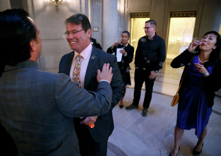 "Newlyweds Peter Shields (left) and Raul Hernandez embrace after exchanging vows at San Francisco City Hall as friend Robin Nakamura blows bubbles. ""It is a demonstration of my full commitment to him,"" Hernandez said."