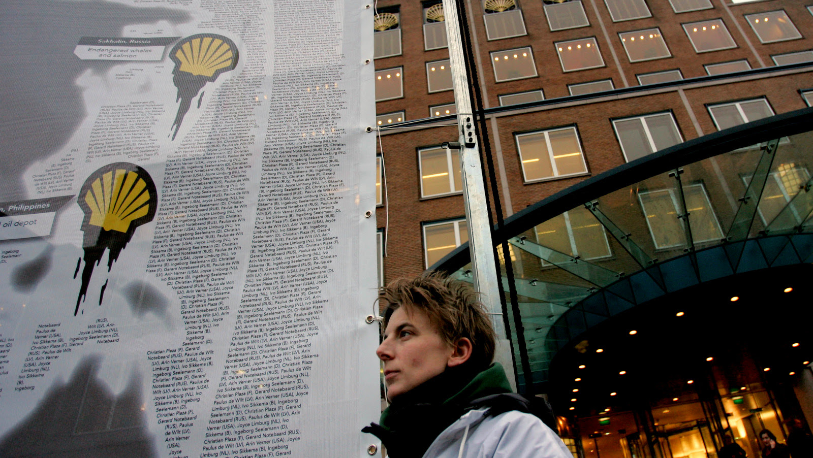 A demonstrator stands besides a banner with a Shell logo dripping oil, outside the Royal Dutch Shell PLC headquarters, rear, in The Hague, Netherlands. (AP/Peter Dejong)