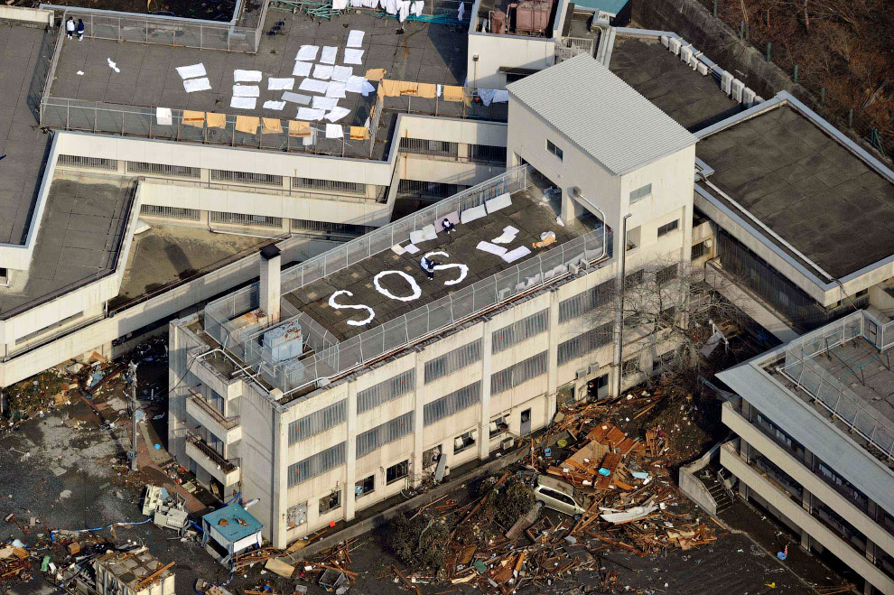 Люди из бумаги выложили слово SOS на крыше здания в Кесеннуме, префектура Мияги