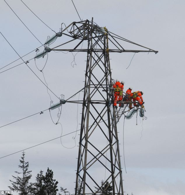 Workers are pictured repairing a damaged pylon in Kintyre, Scotland as communities face a sixth day without power