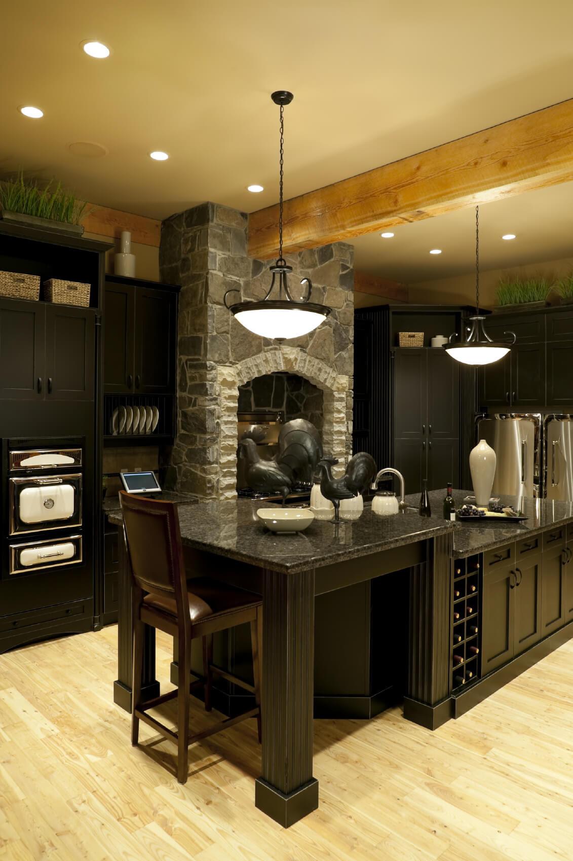 Cuisine de luxe noire avec îlot à 2 niveaux et poutres apparentes au plafond en bois clair