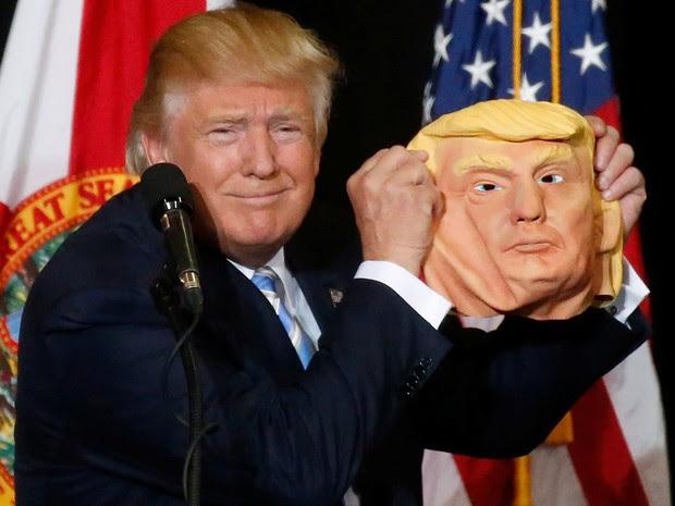 Donald Trump brinca com uma máscara no palco de um comício em Saratosa, na Flórida, na segunda (7) (Foto: Reuters/Carlo Allegri)