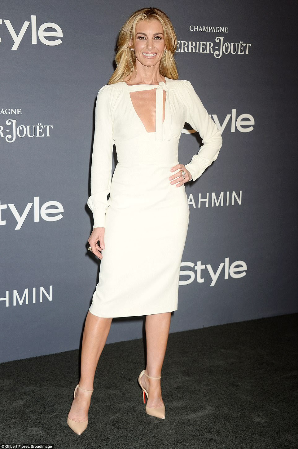 Looking good: Country music star Faith Hill, 50, wore a white long-sleeved dress with a peek-a-boo bodice and nude heels