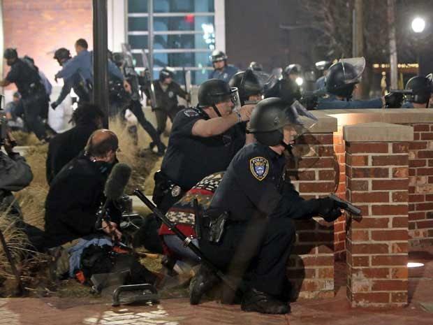 Policiais se protegem durante tiroteio em Ferguson. (Foto: St. Louis Post-Dispatch / Laurie Skrivan / Via AP Photo)