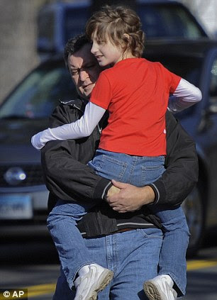 A man carries a child away from the area of a shooting at the Sandy Hook Elementary School
