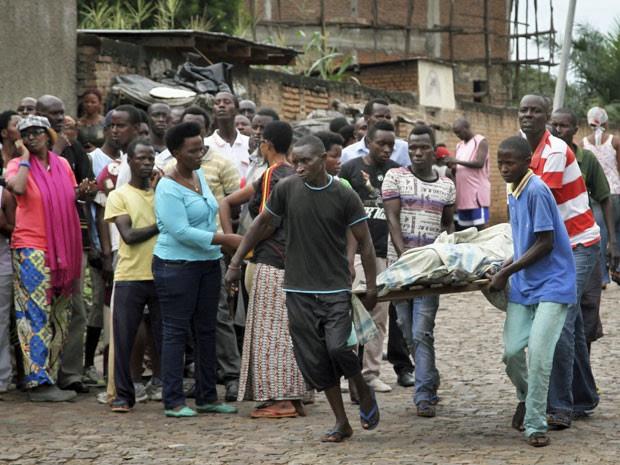 População carrega corpo no bairro de Nyakabiga em Bujumbura, no Burundi. (Foto: AP Photo)