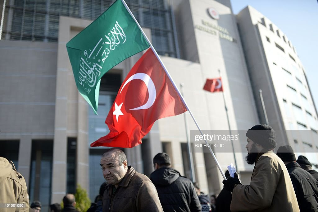 A Muslim protestor holds Turkish and Islamic flag in front of ...