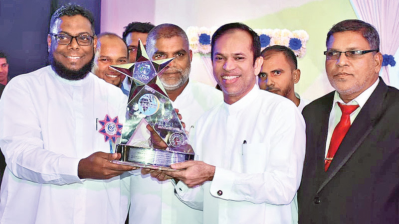 Minister M. L. A. M. Hisbullah presenting an award to a social worker.
