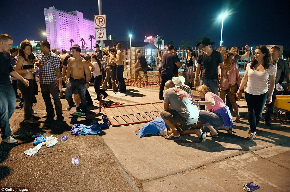 People tend to the wounded outside the festival ground after the shooting. One person can be seen with a shirt draped over their face; it's not clear if they are dead