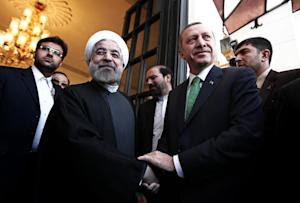 Iranian President Hassan Rouhani (L) shakes hands with …