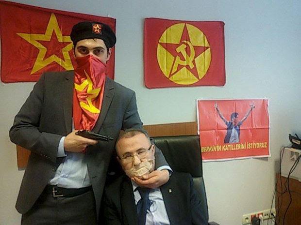 Criminoso armado posa com o promotor Mehmet Selim Kiraz, feito refém em Istambul nesta terça-feira (31) (Foto: Halkin Sesi TV/Reuters)