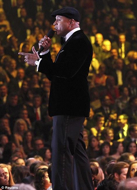 Crooners: Maroon 5 Adam Levine frente homem entretém a multidão, enquanto, à direita, o apresentador do programa LL Cool J aborda o público