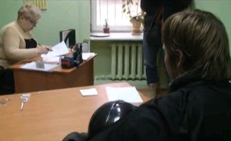 Action stations: The unmasked crusader is handed a form by an official in Odessa
