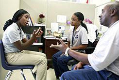 Lafayette Academy Charter School social workers Kellie Dejan, center, and Steve Dooley meet with Jocylra Wilson, 12.