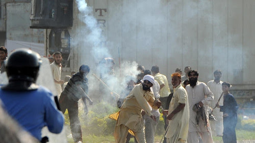 Pakistan protesters throw teargas cannisters back at riot police. Five people were killed in anti-US demonstrations on September 21, 2012. by Pan-African News Wire File Photos