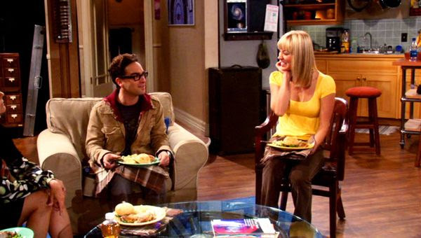 Leonard and Penny turn to look at each other after Mary Cooper (visible near the left of frame) tells them that they make a cute couple in THE BIG BANG THEORY.