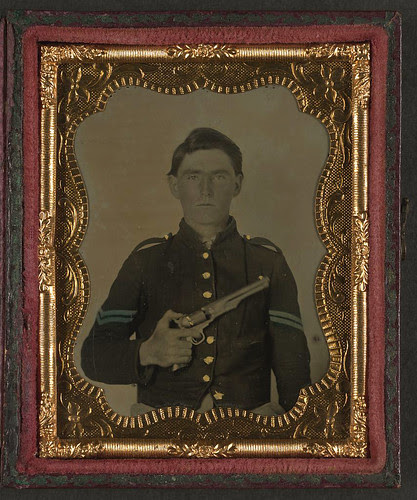 [Unidentified soldier in Union corporal's uniform holding Colt revolver to chest] (LOC)