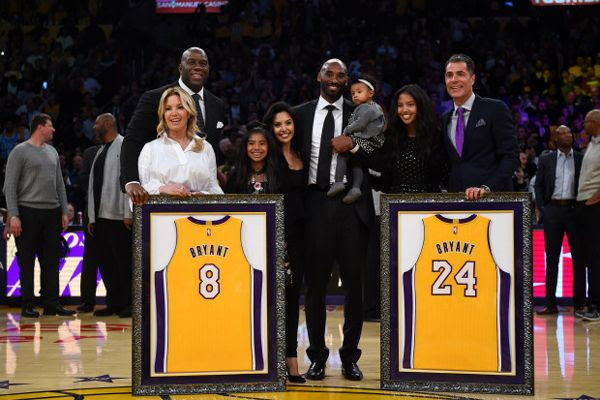 Kobe Bryant poses with his family as well as Jeanie Buss, Magic Johnson and former agent Rob Pelinka during Bryant's jersey retirement ceremony at STAPLES Center...on December 18, 2017.