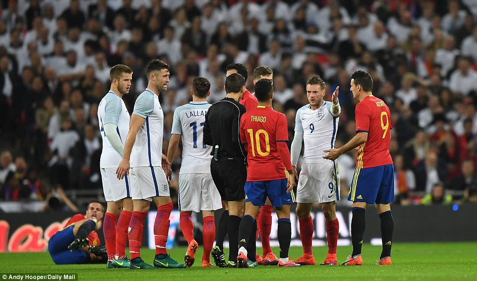 England and Spain's players gather around the referee early into the feisty first half of the international friendly match