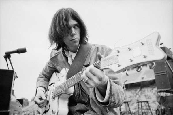 December 1969, San Diego, California, USA --- Neil Young plays his vintage Gretsch White Falcon during a sound check at Balboa Stadium just before a Crosby, Stills, Nash & Young concert. --- Image by © Henry Diltz