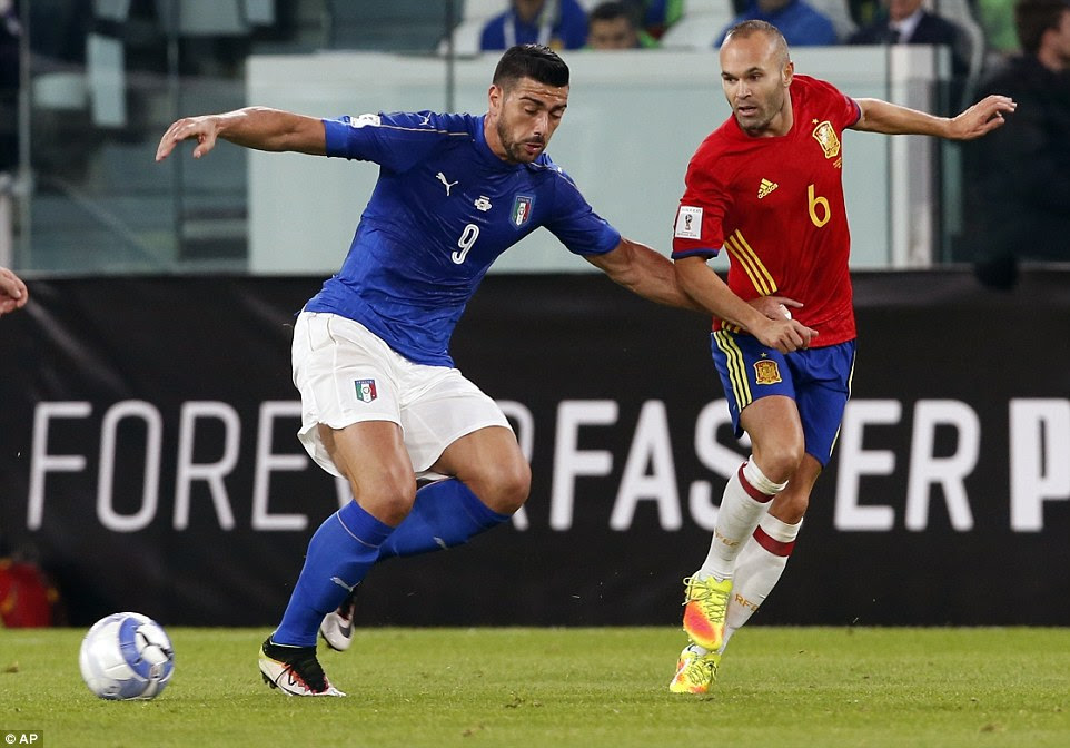 Spain's legendary midfielder Andres Iniesta (right) bewitches Italy's former Southampton strikerGraziano Pelle