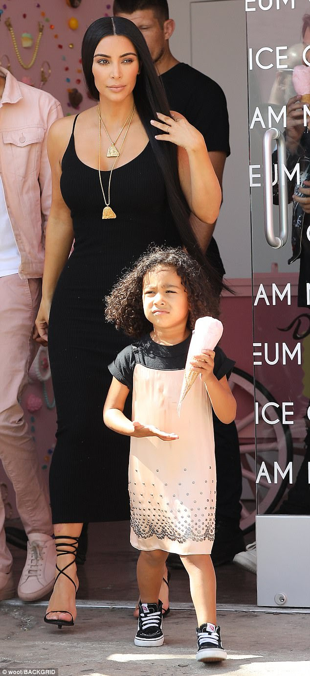 Treat: Kim Kardashian poured her curves into a clingy  sleeveless black knit dress as she treated daughter North to an ice cream cone on Thursday in LA