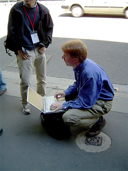 Eric Meyer crouched on a footpath in Sydney with his laptop