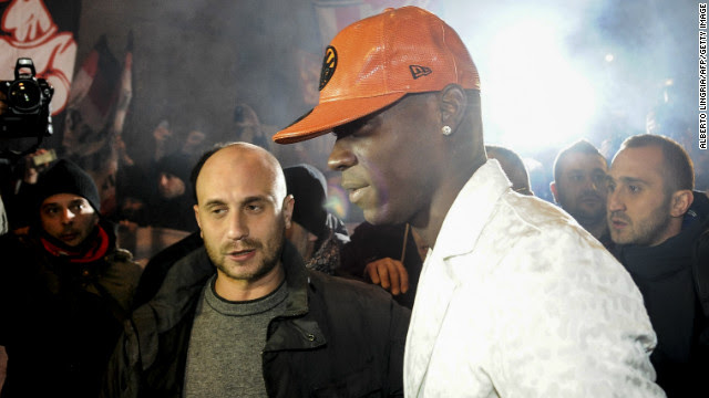 Mario Balotelli was mobbed by fans outside a restaurant as he returned home to Italy ahead of completing his reported $30 million move tom AC Milan from Manchester City.
