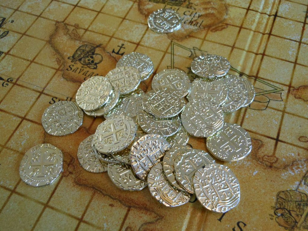 Fancy plastic coins from the Dread Pirate: Buccaneer's Revenge board game, presented on the treasure map game board.