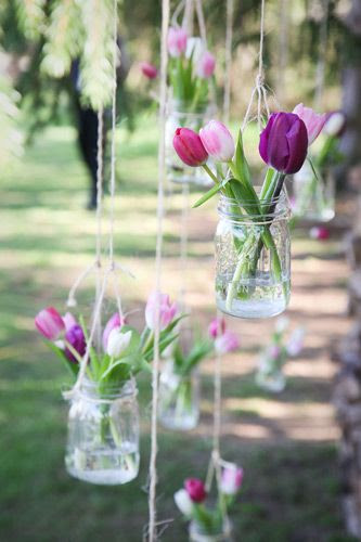 No need for a florist! The women planted tulip bulbs in autumn and the flowers bloomed days before their wedding. Their cousins had the creative idea to hang mason jars filled with tulips around the area where the women had their ceremony.