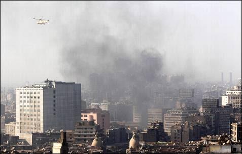 Un helicóptero militar sobrevuela las nubes de humo provocadas por las revueltas en El Cairo.