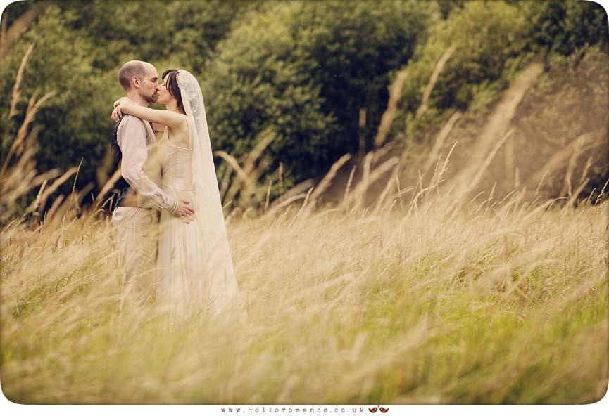 Bride kissing in wheat field