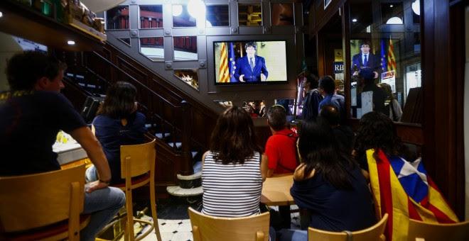 Un grupo de ciudadanos siguen desde una pantalla de televisión la declaración institucional del presidente de la Generalitat, Carles Puigdemont, tras la decisión del Gobierno de aplicar el artículo 155 en Cataluña. EFE/Quique García