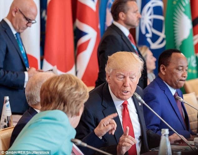 Donald Trump and Angela Merkel appear to be in the middle of a tense conversation at the G7 Summit on Friday
