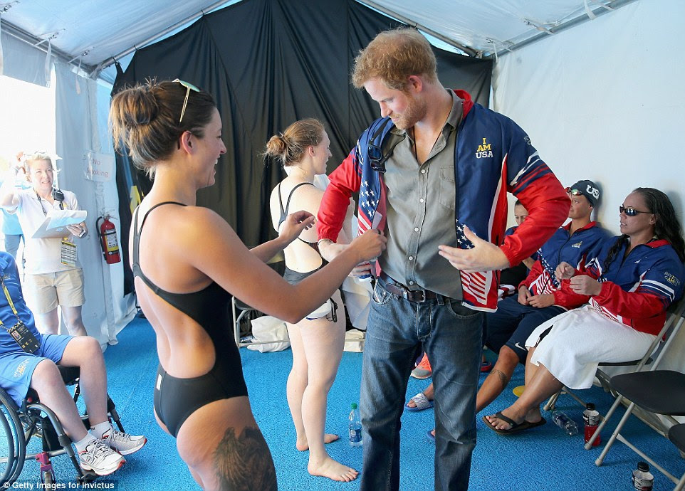 Elizabeth was later seen in stitches as she attempted to kit out Prince Harry in the swimming team's uniform while she stood in the tent in little more than her swimsuit and sunglasses perched on her head