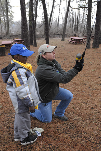 a instructor showing a child how to use a fishing pole