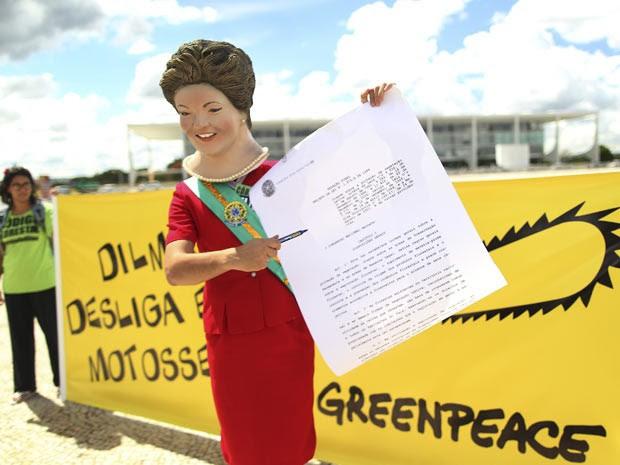 Ator vestido de Dilma Rousseff simula a presidente assinando o veto no Código Florestal, em frente ao Palácio do Planalto, em Brasília. (Foto: Ueslei Marcelio/Reuters)
