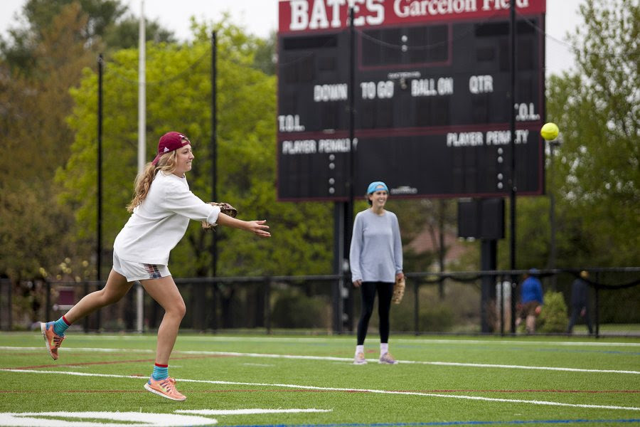 Blair Shrewsbury '14 pitches in the 1st annual John Durkin One Swing Softball Tournament on May 17, 2014, on Garcelon Field. Wally Pierce '14 looks on, at back. Over 2,000 was raised for the John Nolen Durkin Scholarship Fund. (Sarah Crosby/Bates College)